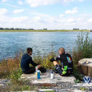 Fietsers lunchen langs het water tijdens de eerste meters